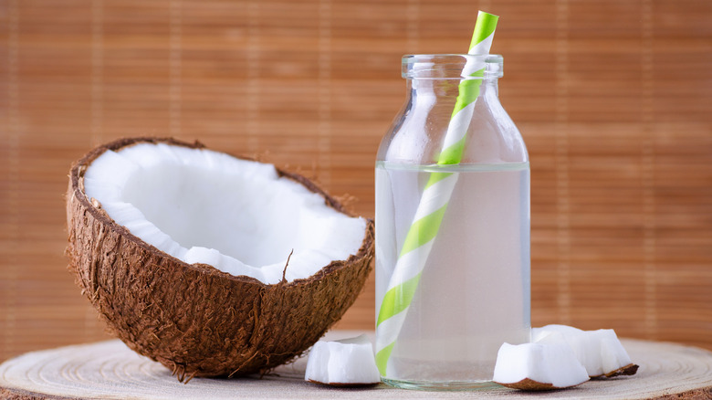 A bottle of coconut water next to a coconut