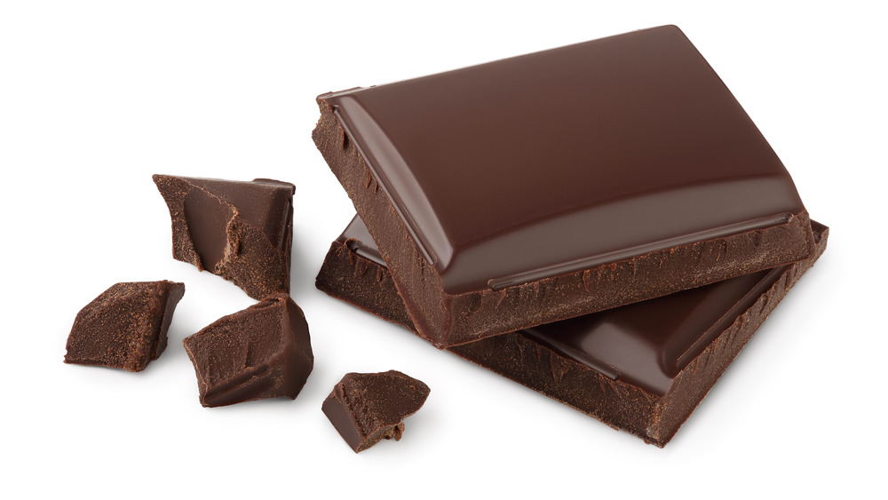 Dark chocolate squares and pieces on white background
