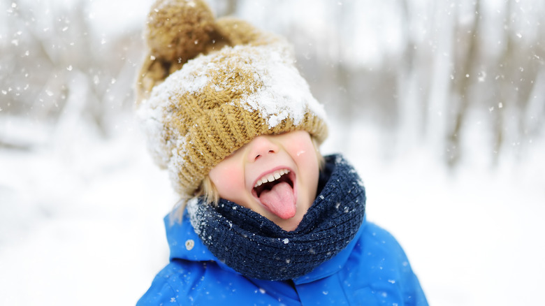 A little kid sticks his tongue out in a snow storm