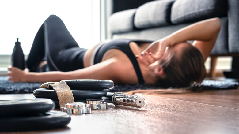 Woman laying on floor tired from workout