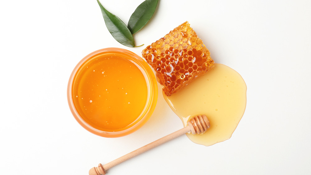 Honey and a honeycomb on a white background
