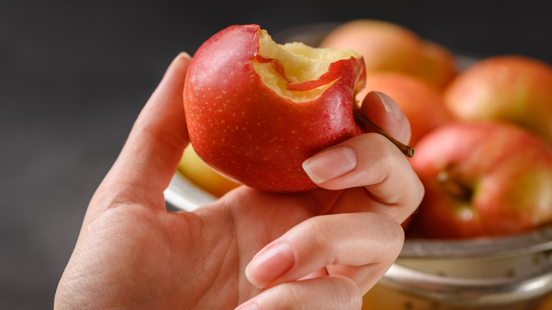 Close up of bitten red apple in hand and bowl full of red apples background