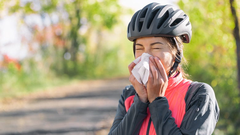 Woman with helmet on blowing her nose into a tissue while on outdoor bike ride