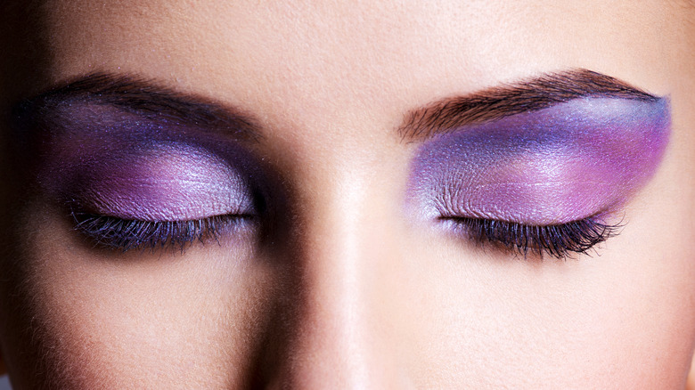Close up of woman with purple eyeshadow on eyelids
