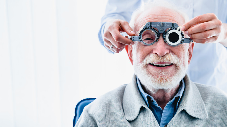 A man smiling as an eye doctor puts a vision testing apparatus over his face
