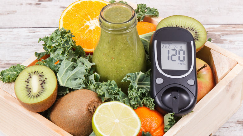 Glucometer with vegetables and fruits in the background