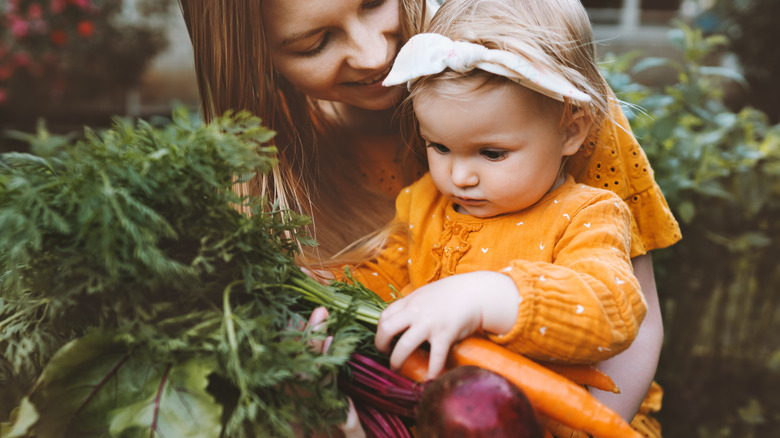 mom and child holding carrots