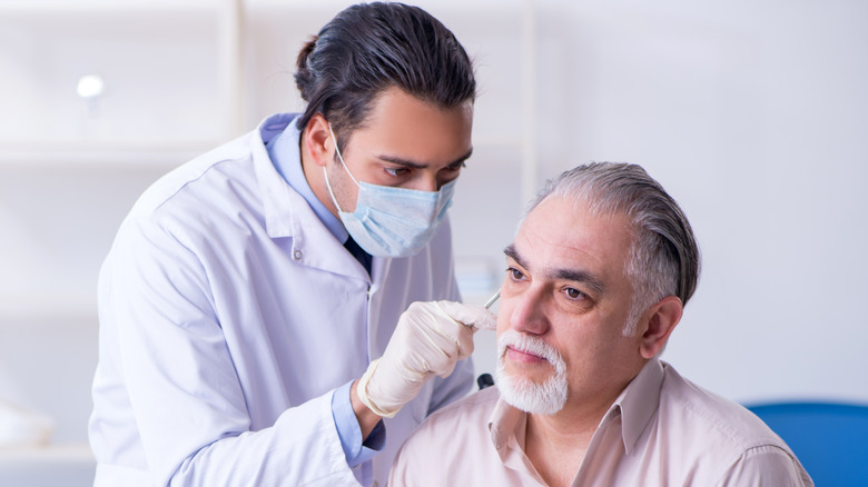Man sitting getting ear checked by doctor wearing a mask and gloves