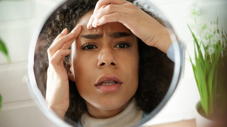 young woman examining her skin in a mirror with a worried expression