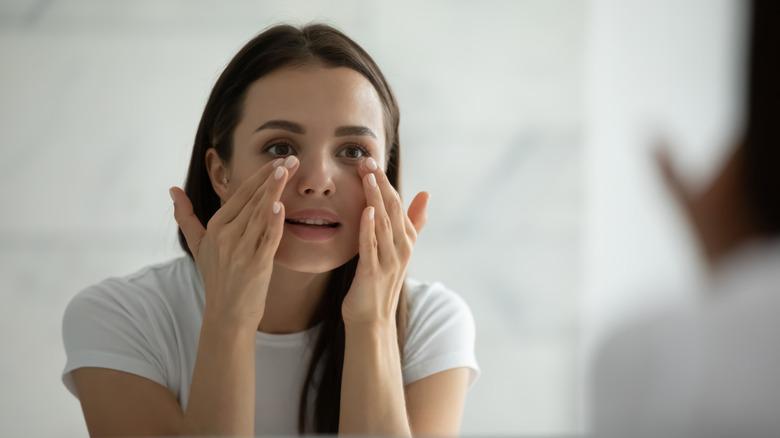 A woman applying under eye cream