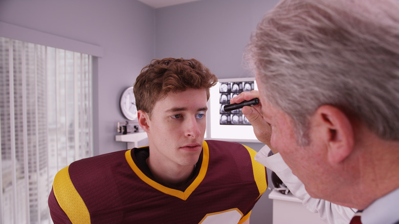 Doctor using flashlight to look at the pupils of a football player