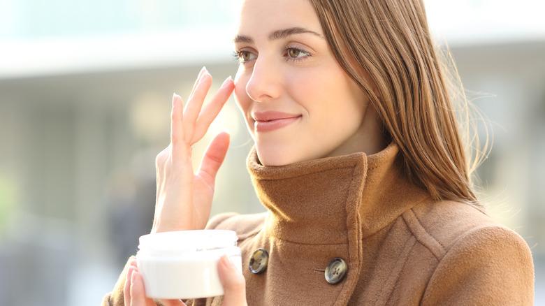 woman putting on retinol cream outside