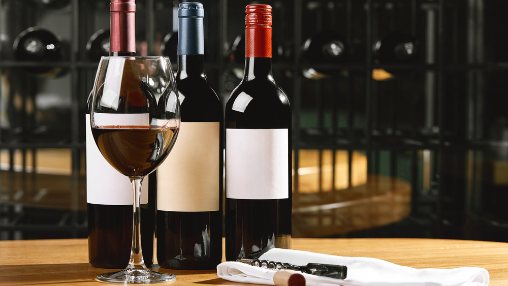 Three bottles of red wine and corkscrew with full glass of wine