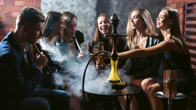Group of smiling friends sitting around a table smoking hookah