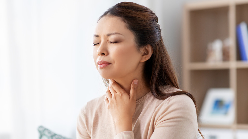 Woman holding her neck, sore throat