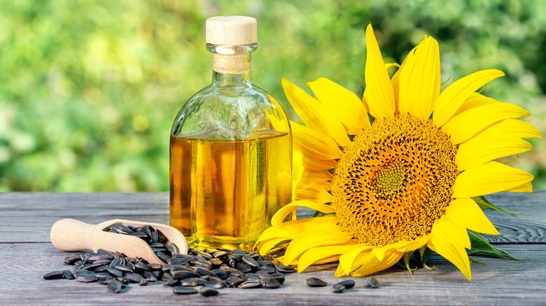 Bottle of sunflower oil next to a sunflower