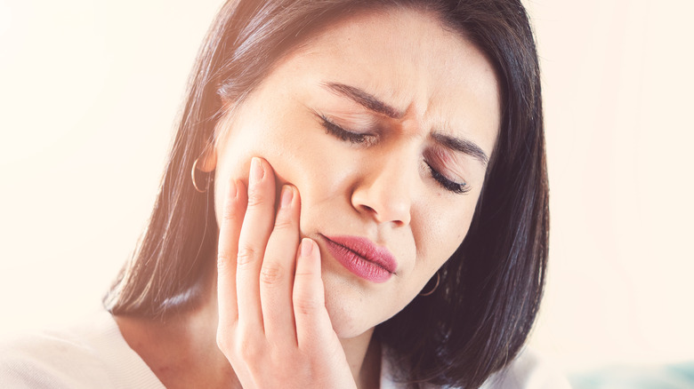 Woman holding her cheek and lower jaw in pain
