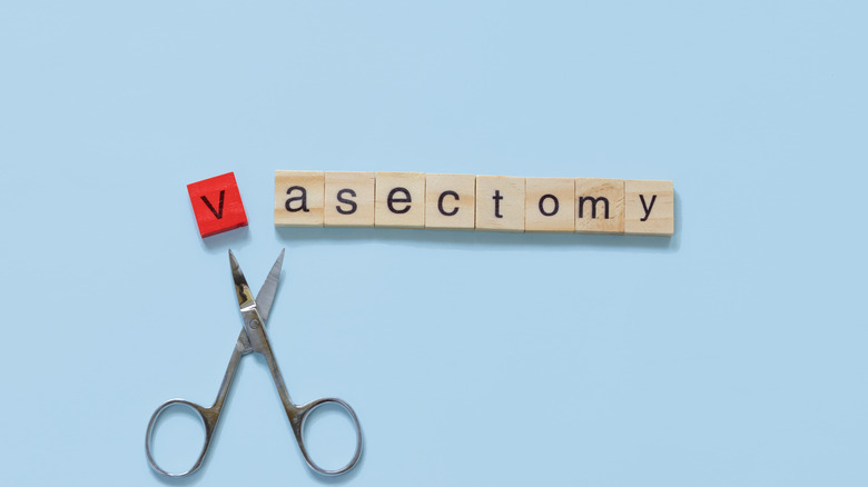 scrabble tiles spelling out 'vasectomy' with miniature scissors