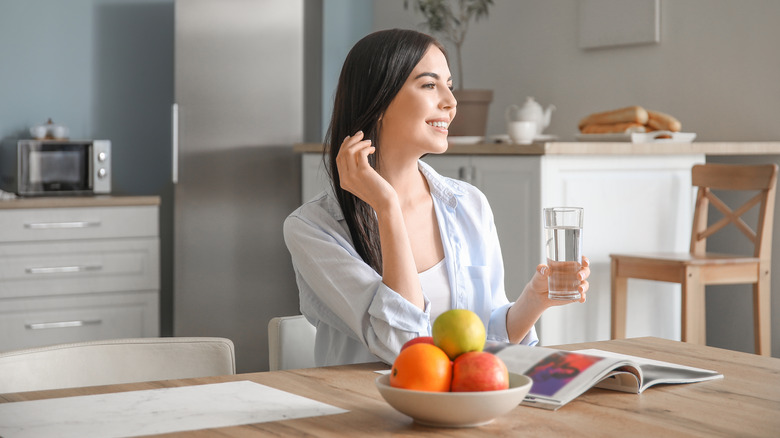 A woman holds a glass of water in her kitchen