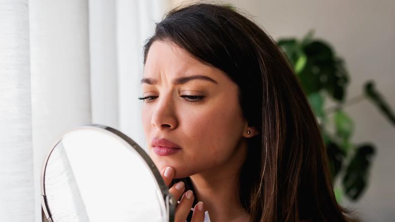 woman examining acne in a mirror