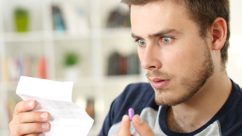 Surprised man reading a leaflet for a medication while holding a pill
