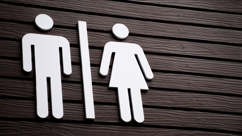 Close up of a sign for public restrooms for men and women on a painted wooden wall