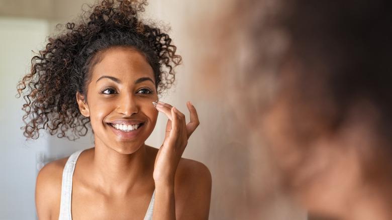 A woman applies face moisturizer