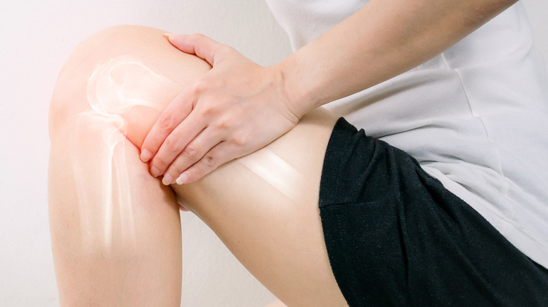 person holding leg with joint pain