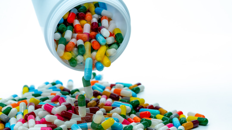 Multi-colored antibiotic capsules pour out of a white pill bottle into a pile