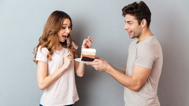 A happy man giving a happy woman a large slice of cake
