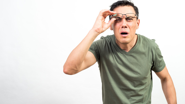 Man squinting while lifting glasses off his nose and having trouble seeing clearly