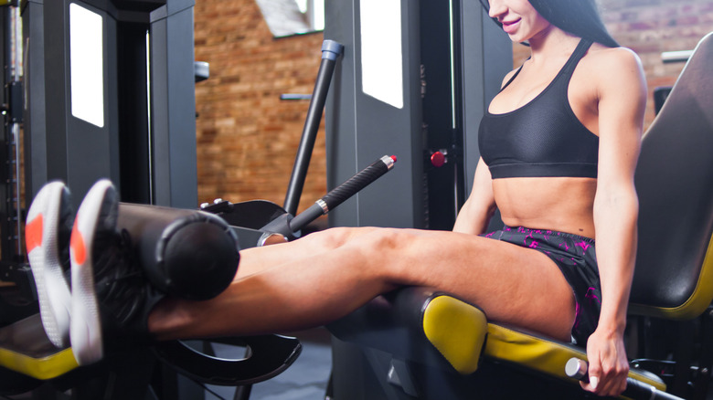 woman training on leg extension machine
