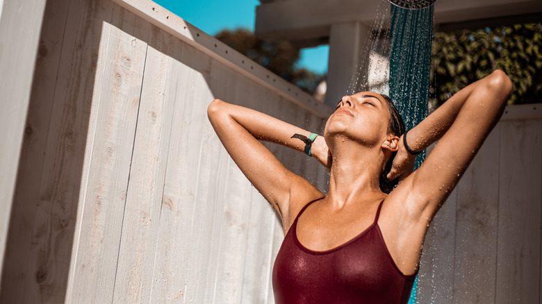 Woman in a red bathing suit showering outside