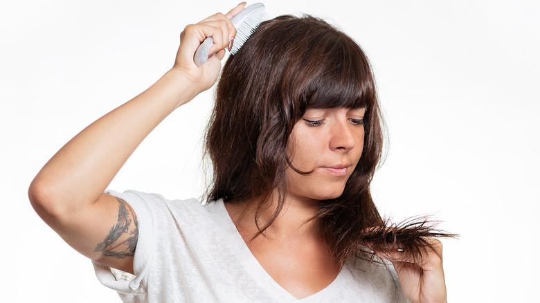 Woman brushing hair and examining split ends