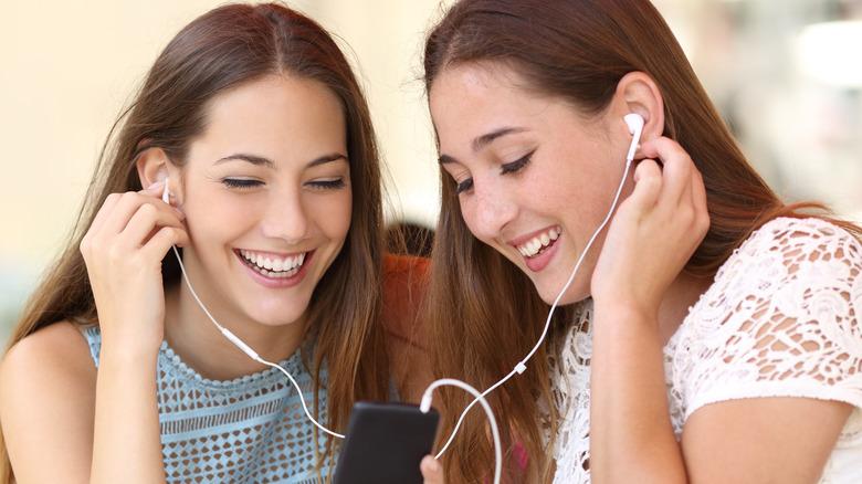 Women sharing earbuds