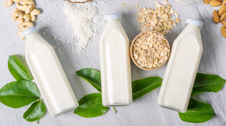 Three glass bottles containing different dairy replacement milks