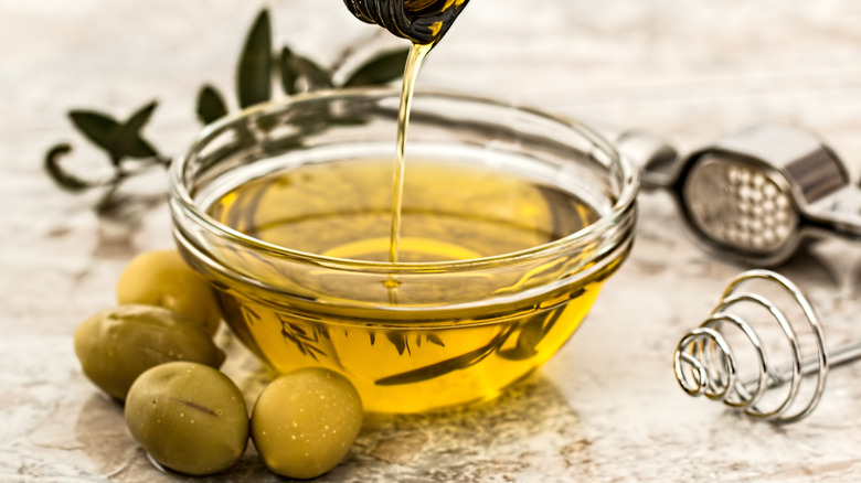 olive oil in a glass bowl with green olives