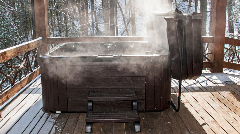 steaming hot tub on wooden deck with snow