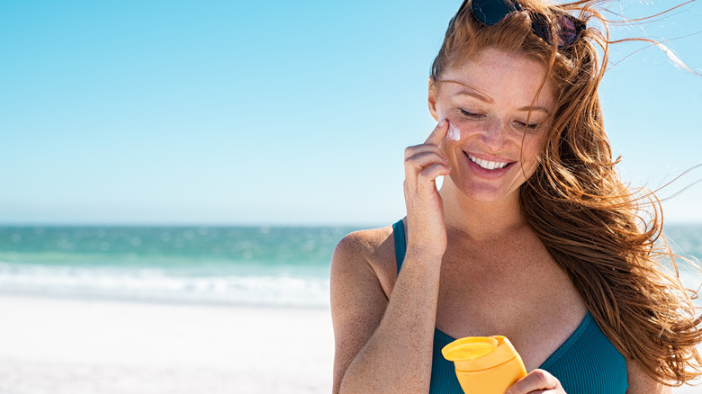 Woman at beach applying sunscreen to face