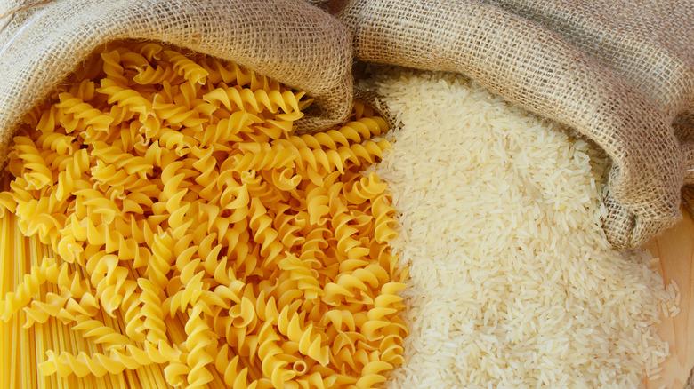 A bag of rice next to a bag of pasta