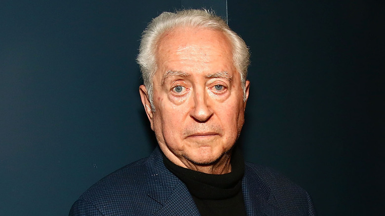 Robert Downey Sr. stands in front of a dark background