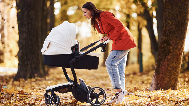 Mother walking with baby in autumn