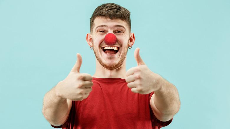 goofy young man wearing a clown nose
