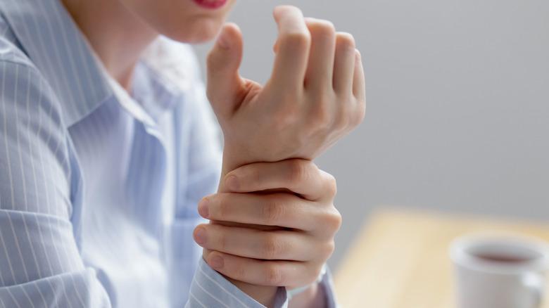 A person grabbing their wrist