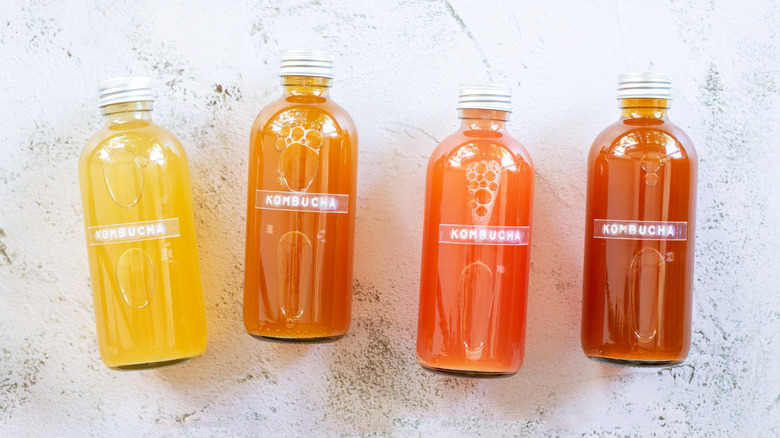 four bottles of kombucha on a white countertop