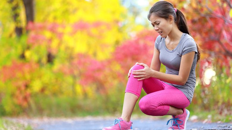 woman runner holding her knee