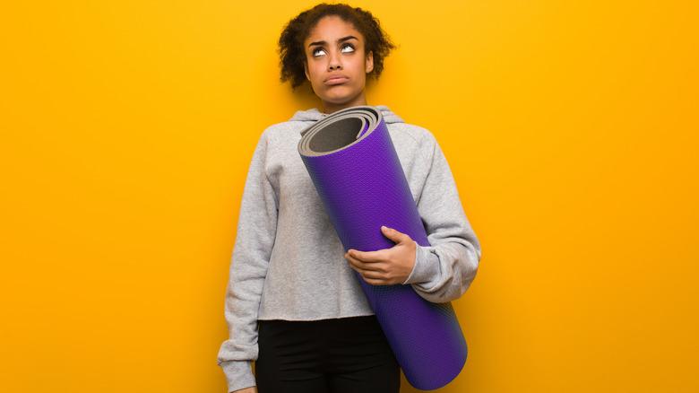 Bored woman holding yoga mat