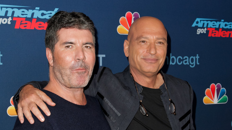 Simon Cowell stands next to Howie Mandel