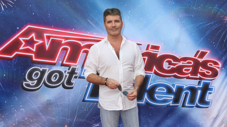 """Simon Cowell stands in front of a sign that reads """"America's Got Talent"""""""