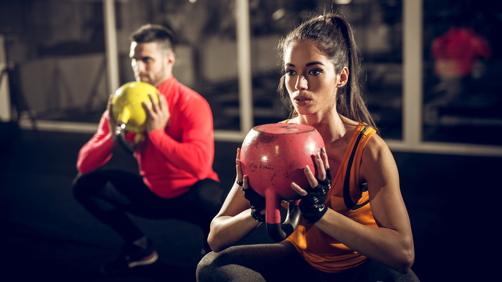A couple doing kettlebell squats in a gym at night